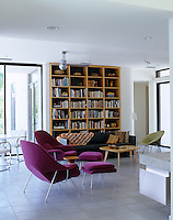A floor-to-ceiling recessed bookcase provides a backdrop to the open-plan living area
