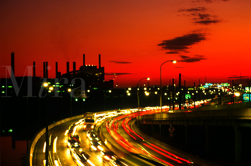 Overview of rush hour traffic at dusk with the smokestacks of a factory in silhouette in the background.