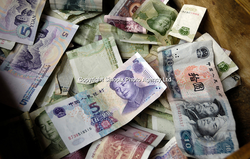A vendor's Chinese RMB spare changes in a Beijing street, China. RMB has risen 9.1 percent since the end of a fixed rate to the dollar in July 2005. The gains will then increase export prices and lower import costs..