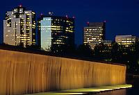 Waterfalls lit at night with Bellevue's Downtown skyline set behind them. Bellevue Downtown Park, Bellevue, Washington.