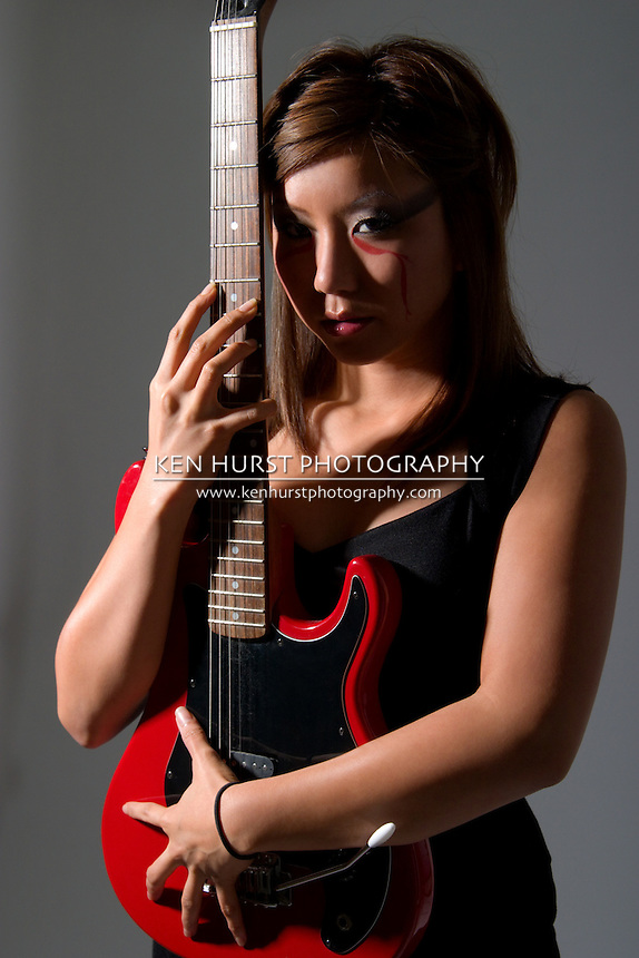 Beautiful girl with exotic makeup holding a red electric guitar.