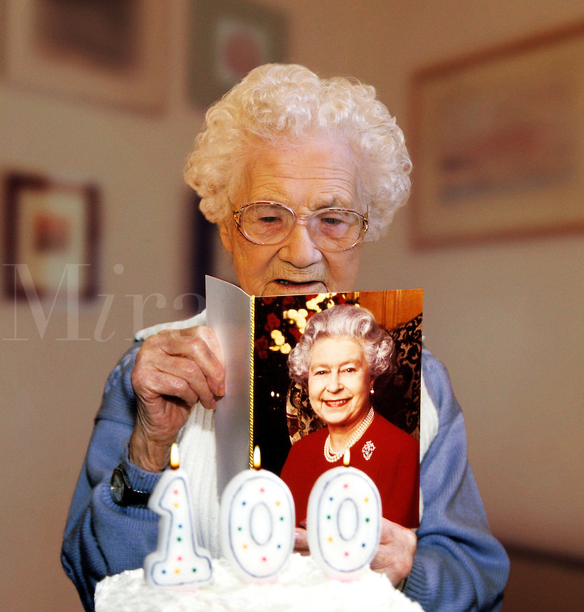 Woman on her 100th Birthday reads a card of congratulations from Queen Elizabeth..