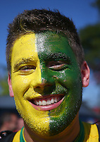 A Brazil fan with a painted face soaks up the atmosphere outside the Itaquerao stadium ahead of kick off in the opening match of the 2014 World Cup vs Croatia