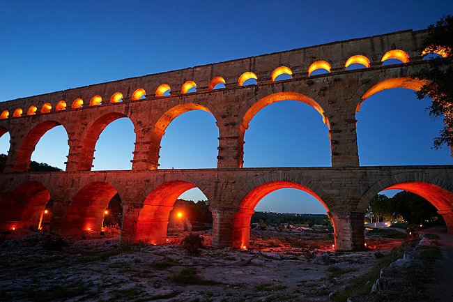 Picture at nightime of the ancient Roman Aqueduct of the Pont du Gard which crosses the River Gardon near Vers-Pon-du-Gard, France. Part of the 50 km long aqueduct that served the Roman town of Nemausus (Nimes) its 3 tiers of arches stand 48 m high (160 ft). A UNESCO World Heritage Site.