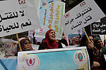 "Palestinian women hold placards and shout slogans during a rally to protest against the rising incidents of violence against women in Gaza City March 03, 2014. Twenty-six women were slain by relatives in the West Bank and Gaza in 2013, twice as many as the year before, according to official figures. The rise stems from mounting economic difficulties in the Palestinian territories, compounded by ongoing leniency for those killing in the name of ""family honor"" and social acceptance of violence against women, women's rights activists said. Photo by Ashraf Amra"