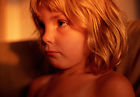 Profile portrait of a young girl with a sad expression.