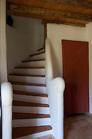 A simple whitewashed staircase with tiled treads in a rustic cottage