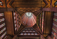 Looking up at the octagonal tower studded with stained glass by Marguerite Hure, in the Eglise Saint-Joseph or St Joseph's Church, built 1951-58 as a memorial to the 5000 citizens of the town who died during the Second World War, designed by Auguste Perret, 1874-1954, and Raymond Audigier, Le Havre, Normandy, France. The church is built from pre-cast concrete, with geometric stained glass windows, a Neo-Gothic interior and a 107m tall tower which acts as a beacon from out at sea. Perret was mentor to Le Corbusier and specialised in the use of concrete. He led the reconstruction of Le Havre in the 1950s, after the town was completely destroyed in WWII. The centre of Le Havre is listed as a UNESCO World Heritage Site. Picture by Manuel Cohen