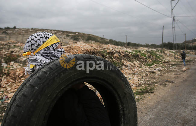 A Palestinian protester carry tires during clashes with Israel security forces following a weekly demonstration against the expropriation of Palestinian land by Israel in the village of Kfar Qaddum, near the West Bank city of Nablus on January 17, 2020. Photo by Shadi Jarar'ah