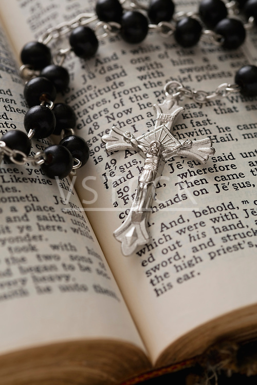 Close-up of open Bible and black rosary beads