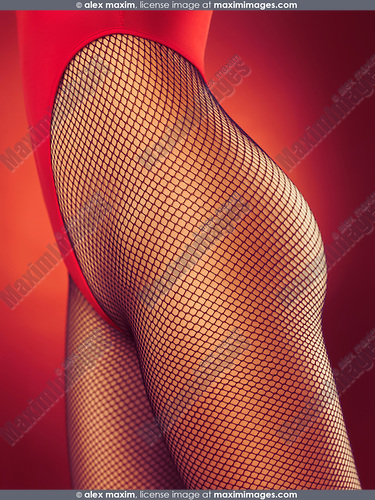 Closeup of a sexy young woman wearing red high-cut double dip swimsuit and fishnet pantyhose on red background