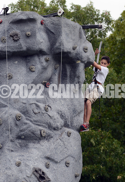 QUAKERTOWN, PA - SEPTEMBER 13:  Ryan Woodman, 12, of Quakertown, Pennsylvania climbs a rock wall during the annual softball tournament and fundraiser for Pride of Quakertown to benefit the organization's youth scholarship program September 13, 2014 in Quakertown, Pennsylvania. (Photo by William Thomas Cain/Cain Images)