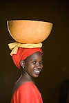 A woman carries a bowl ontop of a specialized headdress in Mali, Africa.