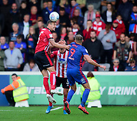 Lincoln City's Jason Shackell heads clear under pressure from  Sunderland's Charlie Wyke<br /> <br /> Photographer Andrew Vaughan/CameraSport<br /> <br /> The EFL Sky Bet League One - Lincoln City v Sunderland - Saturday 5th October 2019 - Sincil Bank - Lincoln<br /> <br /> World Copyright © 2019 CameraSport. All rights reserved. 43 Linden Ave. Countesthorpe. Leicester. England. LE8 5PG - Tel: +44 (0) 116 277 4147 - admin@camerasport.com - www.camerasport.com