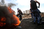 A female Palestinian protester burn tires during clashes with Israeli troops near the Jewish settlement of Bet El, near the West Bank city of Ramallah, October 29, 2015. Israeli security forces shot dead two Palestinian assailants in the occupied West Bank on Thursday, police and the army said, as a month-long spate of stabbing attacks showed no signs of abating. Photo by Shadi Hatem