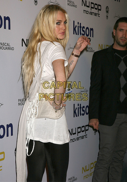 LINDSAY LOHAN.Nu Pop Movement Watch Launch Party at Kitson Men, West Hollywood, California, USA..November 12th, 2009.half length waist belt cincher corset bustier over  black leggings cream white t-shirt top tights back behind rear looking over shoulder hand on hip tattoo .CAP/ADM/MJ.©Michael Jade/AdMedia/Capital Pictures.