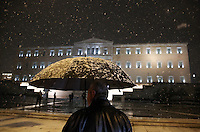 Pictured: A man with an umbrella walks past the Greek Parliament in Syntagma Square, Athens, Greece. Monday 09 January 2017<br /> Re: Heavy snow fall and minus zero temperatures have affected most parts of eastern Europe and Greece.