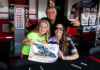 May 30, 2014; Englishtown, NJ, USA; A young fan poses with NHRA funny car driver Alexis DeJoria and drag racing artist Kenny Youngblood during qualifying for the Summernationals at Raceway Park. Mandatory Credit: Mark J. Rebilas-