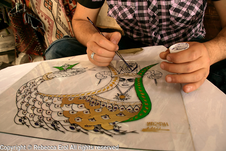 Local artisan painting a shahmaran, Mardin, Turkey. The mythical goddess is painted on glass