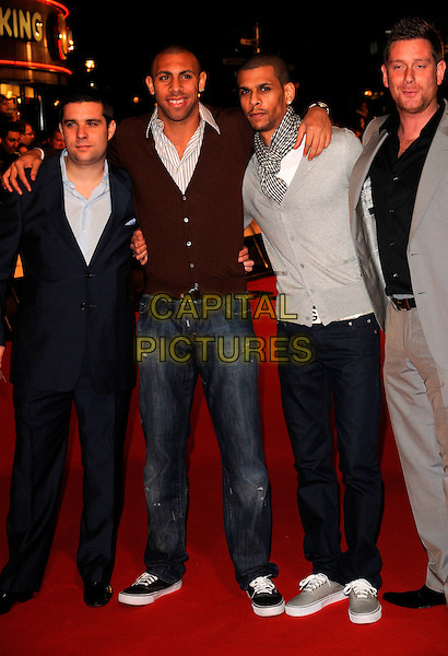 "ANTON FERDINAND (2nd left) & GUESTS.The UK gala premiere of ""Rambo"", Vue Cinema, Leicester Square, London, England. .February 12th, 2008.full length jeans denim black jacket brown cardigan scarf .CAP/CAN.©Can Nguyen/Capital Pictures."