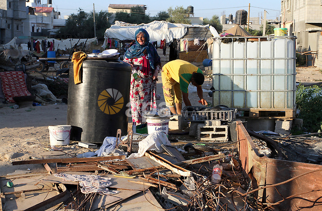 A Palestinian woman works outside her container where is temporary living after hundreds of homes were destroyed during the 2014-summer Israeli war on Gaza Strip, in the third day of the Muslim holiday of Eid Al-Fitr that marks the end of Ramadan, in Khuzaa, in the east of the town of Khan Younis in southern Gaza Strip, on July 19, 2015. Photo by Abed Rahim Khatib