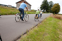 Polish dad with two sons bicycling down country road. Zawady Central Poland