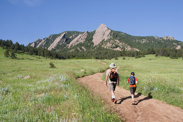 Caucasian father and son hiking towards the Flatirons rock formation in Chautauqua Park, Boulder, Colorado, USA .  John leads private photo tours in Boulder and throughout Colorado. Year-round.