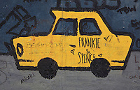 Section of the Berlin Wall depicting a yellow East German Trabant car, detail of a painting entitled Mauern International by Alexej Taranin, damaged by graffiti, part of the East Side Gallery, a 1.3km long section of the Wall on Muhlenstrasse painted in 1990 on its Eastern side by 105 artists from around the world, Berlin, Germany. Picture by Manuel Cohen