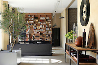In the spacious loft-style living area a whole wall is covered in open bookshelves