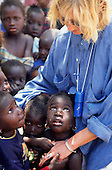 Banjul, The Gambia. Female tourist meeting a group of local children.
