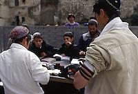 ISRAELE, Gerusalemme: un gruppo di ragazzini prega e legge libri sacri in strada. Un ragazzo più grande li osserva con il tefillin avvolto al braccio.