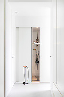 A built in storage cupboard with a sliding door at the end of a hallway. A clever idea for storing a bicycle vertically saves space.
