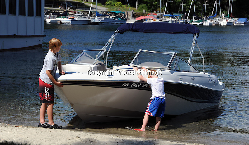 Two boys tending the family boat in the harbor in Sunapee, New Hampshire USA