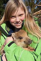 Wildschwein, Mädchen, Kind mit verwaistem Jungtier im winterlichen Garten, wird in menschlicher Obhut großgezogen, Jungtier wird von Hand aufgezogen, Aufzucht eines Wildtieres, Wild-Schwein, Schwarzwild, Schwarz-Wild, Frischling, Junges, Jungtier, Tierkind, Tierbaby, Tierbabies, Schwein, Sus scrofa, wild boar, pig