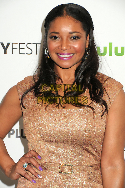 """Tamala Jones.PaleyFest 2012 Presents """"Castle"""" held at The Saban Theatre, Beverly Hills, California, USA, 9th March 2012..half length gold dress hand on hip  belt  smiling .CAP/ADM/BP.©Byron Purvis/AdMedia/Capital Pictures."""