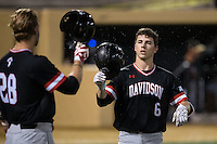 Eric Jones (6) of the Davidson Wildcats knocks helmets with teammate Brian Fortier (28) after hitting a home run against the Wake Forest Demon Deacons at David F. Couch Ballpark on February 28, 2017 in Winston-Salem, North Carolina.  The Demon Deacons defeated the Wildcats 13-5.  (Brian Westerholt/Four Seam Images)
