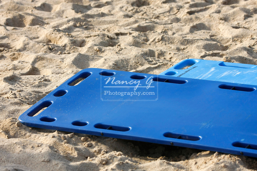 EMS medical backboards laying in the sand at a site of a mass casualty incident