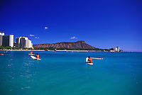 Scenic Diamond Head crater in background. Surfers wait for waves off waikiki beach with a clear view of an hawaiian landmark; Diamond Head. Oahu.