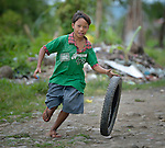 John Mark Dolier, 12, rolls a tire as he runs along a path in the Lao neighborhood of Ormoc, a city in the Philippines province of Leyte that was hit hard by Typhoon Haiyan in November 2013. The storm was known locally as Yolanda. Lutheran World Relief and other ACT Alliance members have been providing a variety of forms of assistance to survivors here, including an LWR-sponsored cash for work program that has allowed residents to recover more quickly.
