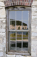 The towering limestone cliffs reflected in one of  the historic building windows at Fayette Historic State Park in Michigan's Upper Peninsula.