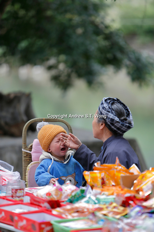 An elderly woman of the ethnic Bouyei Tribe comforts a crying toddler at Wangmo County in China's southwestern Guizhou Province, April 2019.