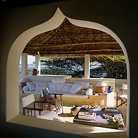 A roof terrace shaded by a traditional makuti thatched roof is furnished with piles of siesta-inducing cushions and soft mattresses