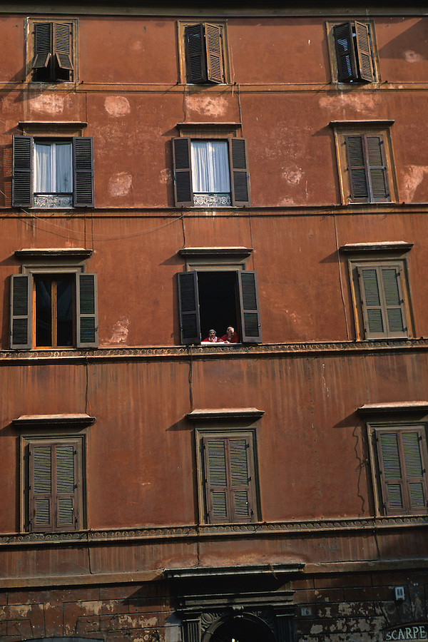 A couple in Rome, Italy, enjoy gazing out the window of their building.