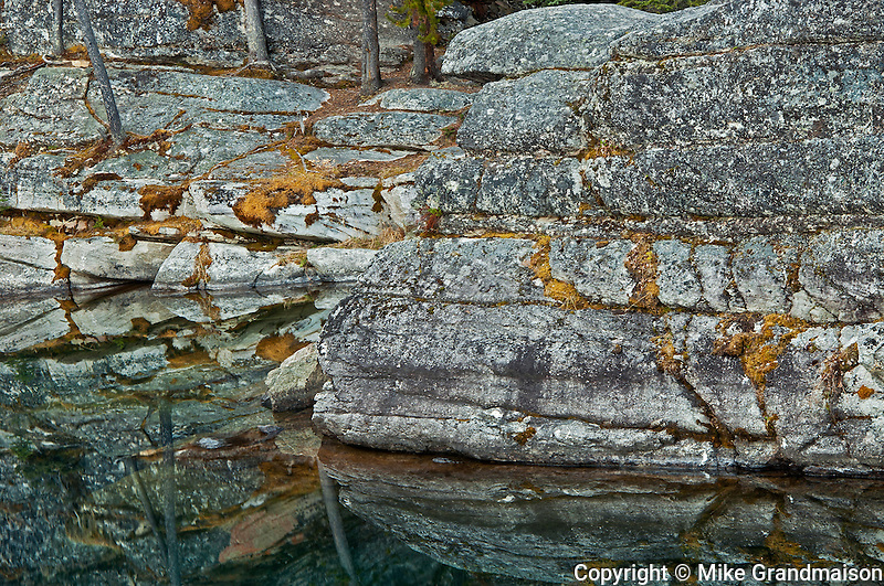 Rocky shoreline reflected in Horseshoe Lake<br /> Jasper National Park<br /> Alberta<br /> Canada