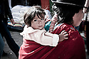 An indigenous woman carries her young daughter through a market in Otavalo, Ecuador.
