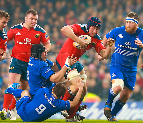29.03.2014 Dublin, Ireland.  Tommy O'Donnell (Munster) charges through the tackles of Eoin Reddan (Leinster) and Mike Ross (Leinster) during the RaboDirect Pro 12 game between Leinster and Munster from Aviva Stadium.