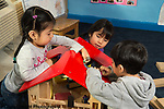 Education Preschool 4 year olds two girls and a boy playing with doll house and small figures