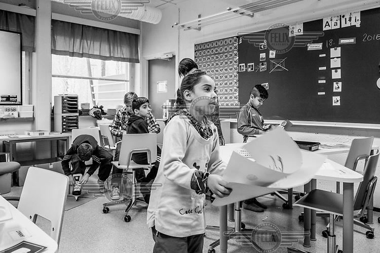 Jannat Mohamad, a refugee girl from the Tarina refugee shelter, carries some of her work through the classroom. The school has a mixed intake from the indigenous population and children from the town's refugee shelter.