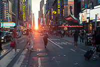 Visitors to Times Square in New York pass the Manhattanhenge sunset on Thursday, May 31, 2012. Twice a year, this year on May 30 and July 12, the sun lines up at sunset with the city's grid, lighting up both sides of the street and setting in the middle of the roadways. The event, the name coined by Neil deGrasse Tyson of the Hayden Planetarium, takes place 22 days before and 21 days after the summer solstice because of the 30 degree angle of the city's grid, it is not exactly east-west-north-south. (©  Richard B. Levine