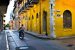 A resident on a motor scooter in Casco Viejo or the old quarter in Panama City, Panama. The neighborhood is a UNESCO World Heritage Site with its old brick paved streets and colorfully preserved colonial architecture.